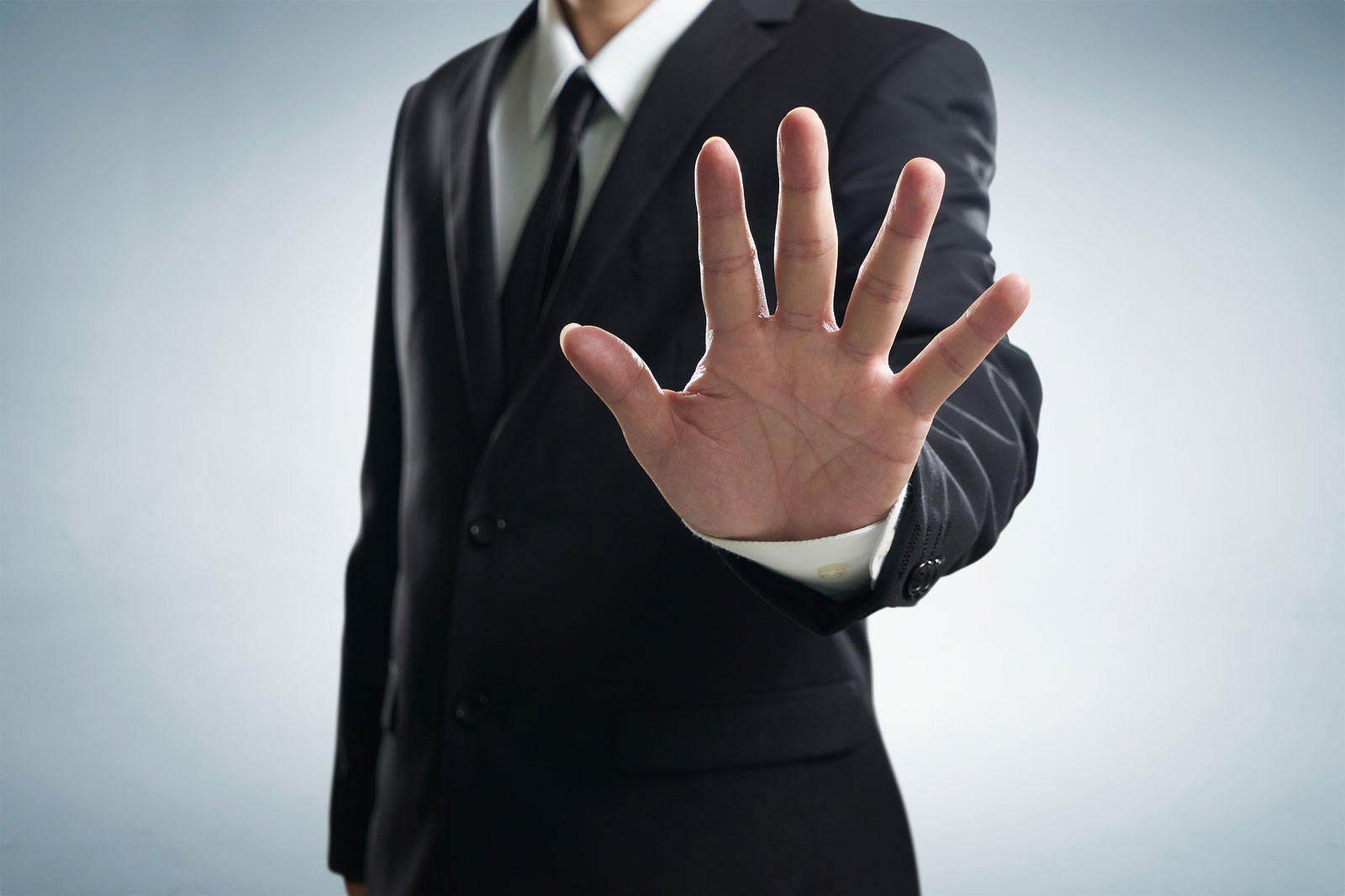Businessman holding up hand showing no