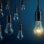 Dull light bulbs with one lit bulb