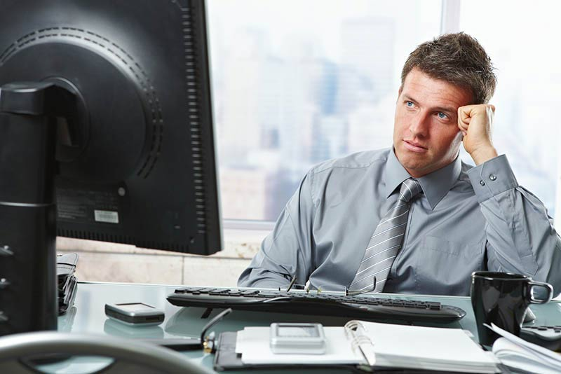 Mid-adult businessman making difficult decision looking at screen