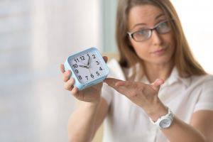 Businesswoman holding clock