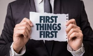 Businessman holding First Things First sign