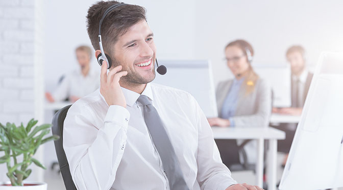 Smiling customer service representative using headset and computer at work