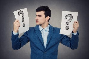 Businessman holding two question marks