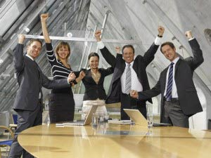 Five business executives cheering in a board room
