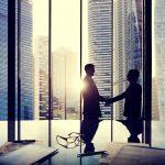 Handshake agreement on skyscraper background