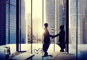 Handshake agreement on skyscraper background