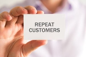 Businessman holding card saying repeat customers