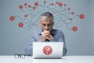 Businessman sat at desk with question marks