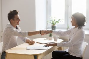 Saleswoman shaking hands with client