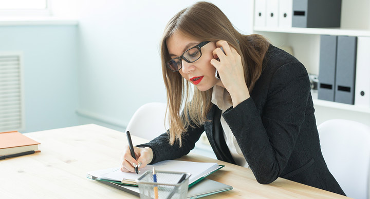 Young woman talking on the phone and making notes
