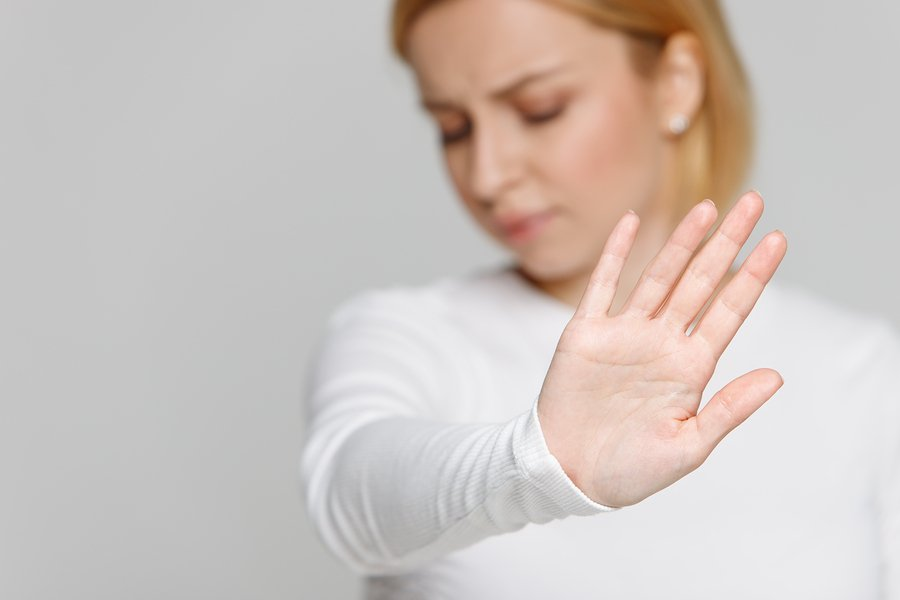 Close up of angry woman refuses offer, showing a gesture of refusing junk food,  rejects something unpleasant, selective focus. Negative emotion, hand gestures.